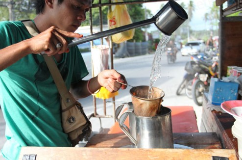 Pouring water over coffee at the side of the street