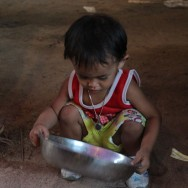 Small Thai boy playing with steel pan at local market